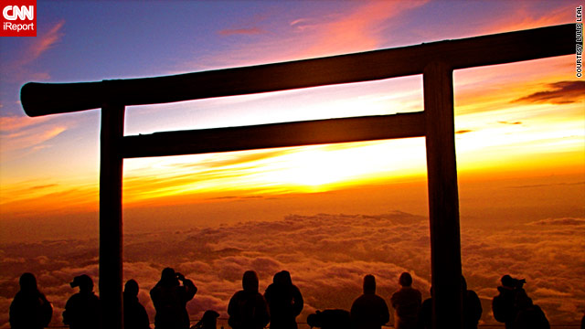 A group of tourists watch the sun rise from the top of Japan's iconic Mount Fuji.