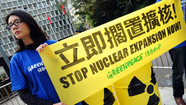 Members of environmental action group Greenpeace raise concerns in front of the Central Government offices in Hong Kong.