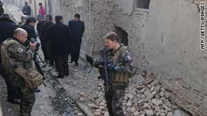 Soldiers with the NATO-led ISAF and Afghan policemen investigate at the site of an explosion in Kabul in January.