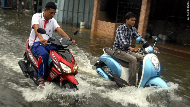 Thai men ride their motorbikes through flood waters following heavy rains in Thailand's southern city of Narathiwat on March 29, 2011.