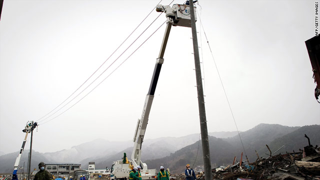 Workers repair damaged electrical cables in Otsuchi. Some blackouts have begun in eastern and northern Japan already.