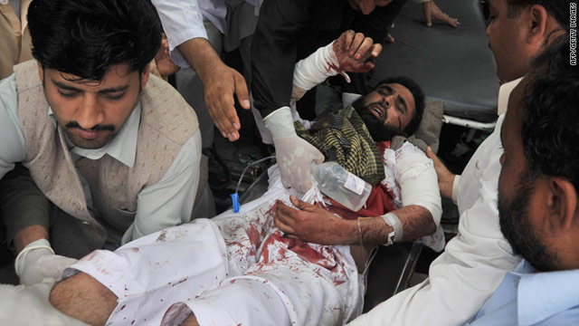 Pakistanis shift an injured victim following a suicide bombing that killed at least 12 people near Peshawar on Thursday.