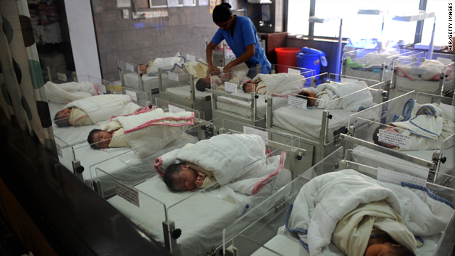 An Indian nurse cares for new born babies in a nursery at a maternity hospital in Kolkata on September 1, 2010.