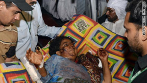 Volunteers carry a blast victim to a hospital in Multan, Pakistan, on Sunday.