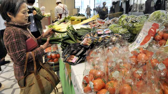 A shopper looks at vegetables for sale, grown in Ibaraki, Chiba, Tochigi and Gunma prefectures on April 6, 2011.