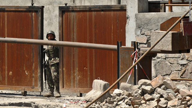 A soldier stands at the main gate of the defense ministry in Kabul, where a gunman killed several staff members Monday.