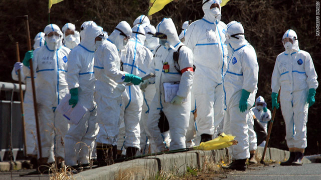 Police in radiation-proof suits on Sunday search for the missing in Namie, Japan, near the Fukushima Daiichi nuclear plant.