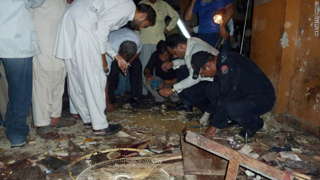 Pakistani policemen examine evidence at a bomb blast site in a gambling building in Karachi on April 21, 2011.