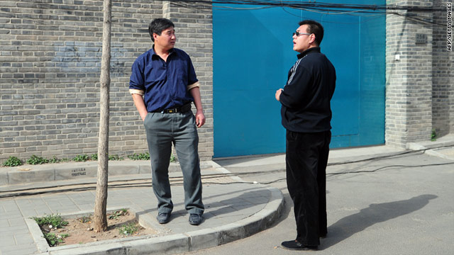 A plainclothes policeman (R) stands in front of the entrance to the studio of outspoken artist Ai Weiwei in Beijing on April 8, 2011.