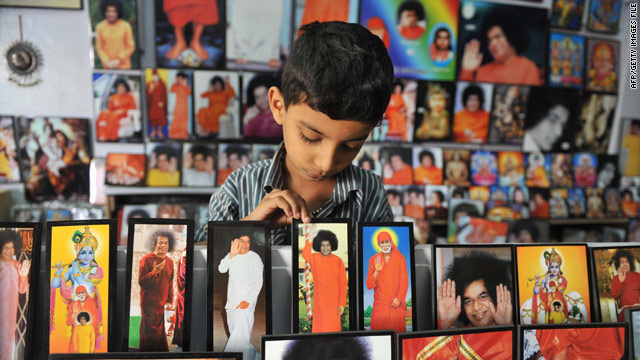 An Indian child looks at portraits of Spirtual Leader Sri Satya Sai Baba at a shop near Prashanthi Nilayam on April 6. One of India's best-known spiritual leaders, known for his apparent miracles and long list of influential followers, died on Sunday.