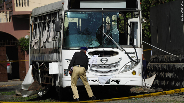 A Pakistani policeman investigates a damaged bus after a bomb attack in Karachi on Tuesday.