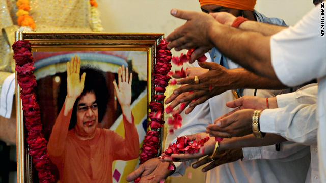 Devotees scatter rose petals during a memorial for Hindu guru Sri Sathya Sai Baba, seen in a framed photograph at left, at the Sri Satya Sai Baba temple in Amritsar on Sunday.