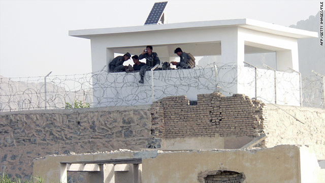 In this photograph taken on June 14, 2008, Afghan policemen sit in a guardhouse at the entrance to the main jail in Kandahar.