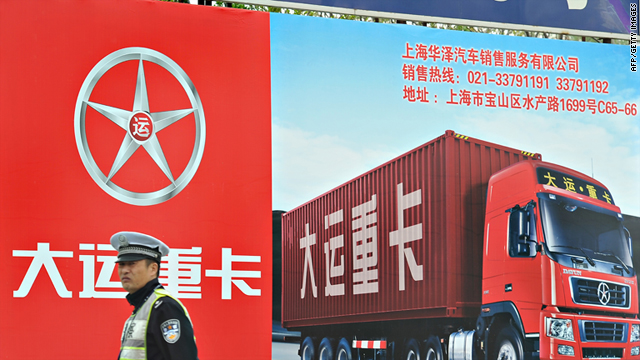 A Chinese policeman stands in front of a billboard of a truck at a port area of Shanghai amid strikes by drivers last week.