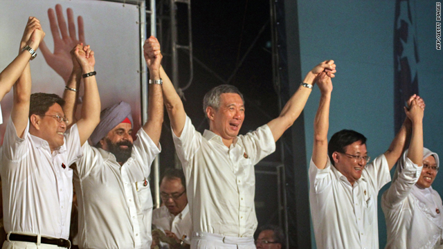 Singapore Prime Minister Lee Hsien Loong, center, of the People's Action Party joins hands with some of his candidates as they celebrate victory in the general election in Singapore early on Sunday.
