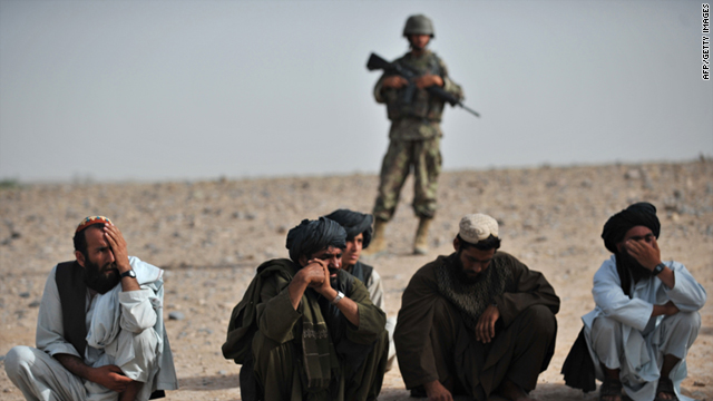 Villagers squat as an Afghanistan National Army soldier stands guard behind them, as unseen U.S. Marines search an abandoned compound belonging to an improvised explosive device maker in Sistani, Helmand Province, on May 12, 2011.