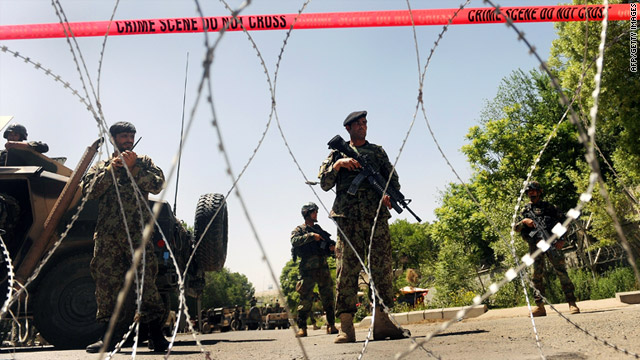 Members of the Afghan military on Saturday stand guard on the road that  leads to the military hospital that was attacked.
