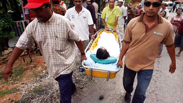 Emergency workers remove a child from an orphanage that was hit by a landslide in Hulu Langat, Selangor, on Saturday.