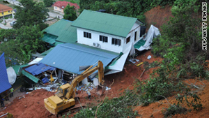Emergency teams work at the site of a landslide that hit an orphanage in Hulu Langat, Selangor, on Saturday.