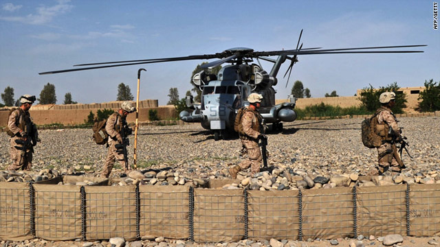 U.S. Marines walk past a Marine helicopter after an early morning operation in Helmand Province on Monday.