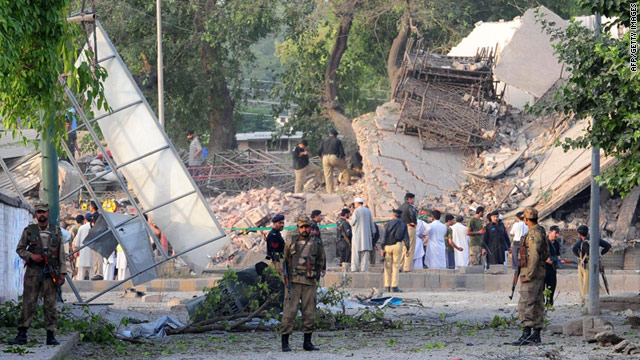 Pakistani security forces gather outside the destroyed police station in Peshawar following the suicide bomb attack.