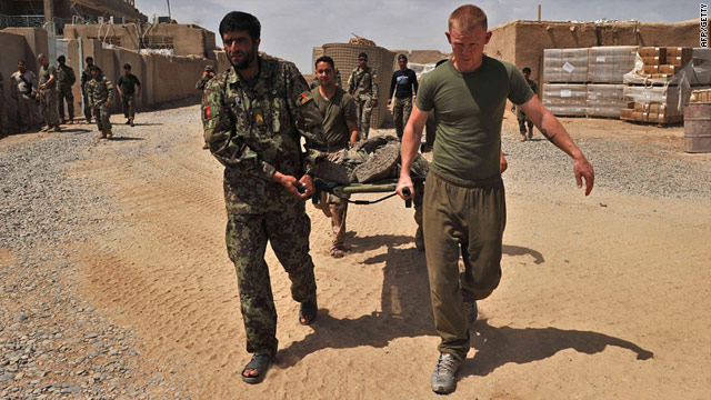 A U.S. Marine and Afghan troops carry a wounded soldier away following a deadly bombing in Helmand Province on Thursday.