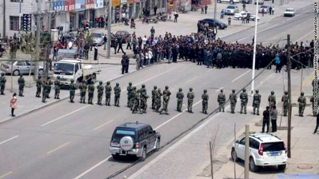 Anti-riot police line up as a crowd gathers in northeastern China on Monday, May 23.