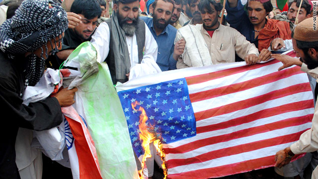 Pakistani protesters hold up a burning U.S. flag during a demonstration against the visit of Hillary Clinton in Lahore on May 27.