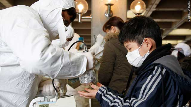 An official scans an evacuated boy to check radiation levels in Koriyama city in Fukushima prefecture on March 16, 2011.