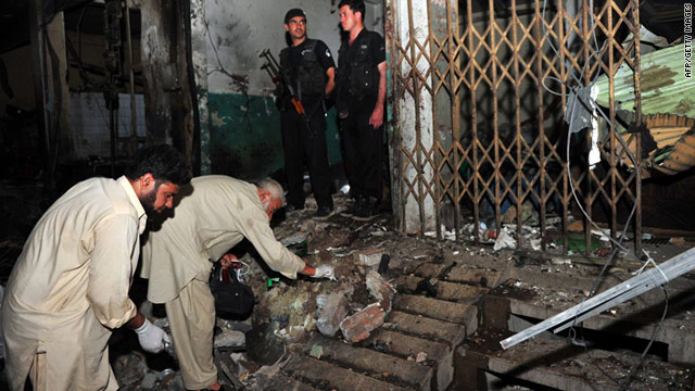 Pakistani security officials examine the site of twin bomb blasts in Peshawar early Sunday.