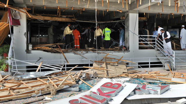 Pakistani security officials examine a damaged Islamabad bank, where a suicide bombing killed a bank guard on Monday.