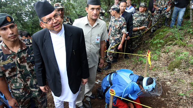 Nepalese PM Jhala Nath Khanal, second from left, observes an army deminer outside Kathmandu on Tuesday.