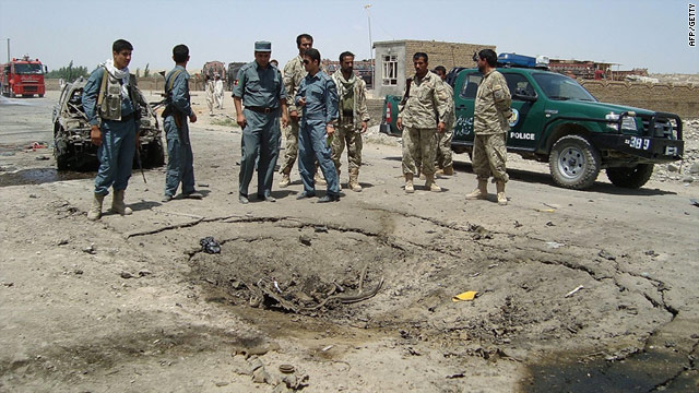 Afghan security forces stand at the site of a suicide car bomb in Kunduz on June 19 which left three Afghan civilians dead.
