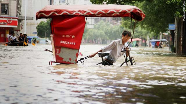 A man rides a bicycle through flood water in Lanxi, east China's Zhejiang province on June 20, 2011.
