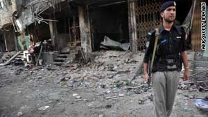 (file photo) A Pakistani policeman stands guard at the site of a bomb blast that hit Peshawar on June 12, 2011.