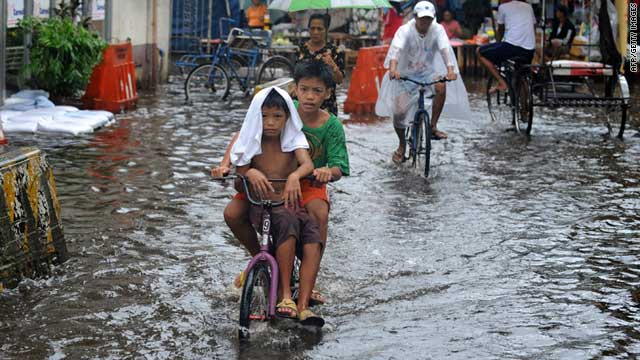 Children pedal their bicycle down a flooded street after heavy rains in Valenzuela City, north of Manila on June 23, 2011.