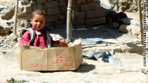 A child plays in a cardboard box at one of the tent cities.