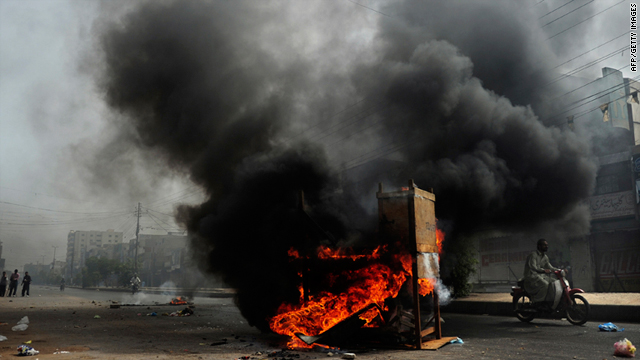 A motorcyclist rides past a pile of burning tires and furniture in a violence-hit neighbourhood of Karachi, Pakistan, on Friday.