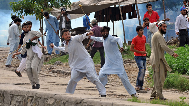 Activists throw stones at police during a march toward the U.S. Embassy in Islamabad on Friday.
