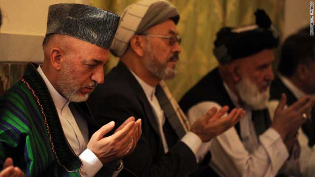 President of Afghanistan Hamid Karzai, left, offers prayers during a funeral ceremony for his late half-brother on Friday.