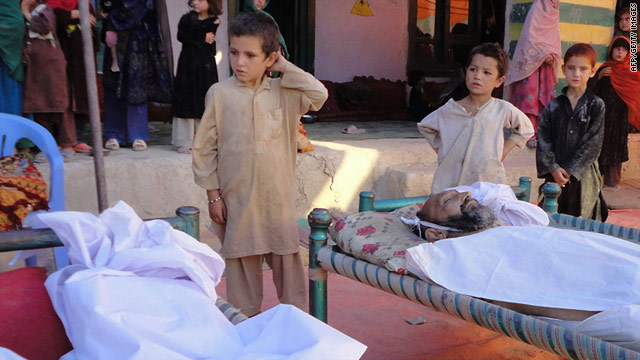 Afghan children stand over the bodies of people purportedly killed in a night raid in Khost province on July 14, 2011.