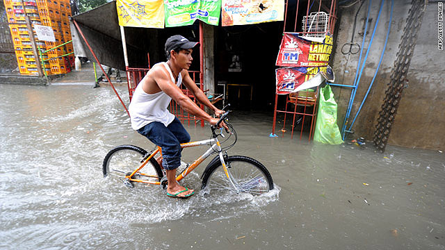 A man rides a bicycle through floodwater after heavy rain in Manila on July 26, 2011.