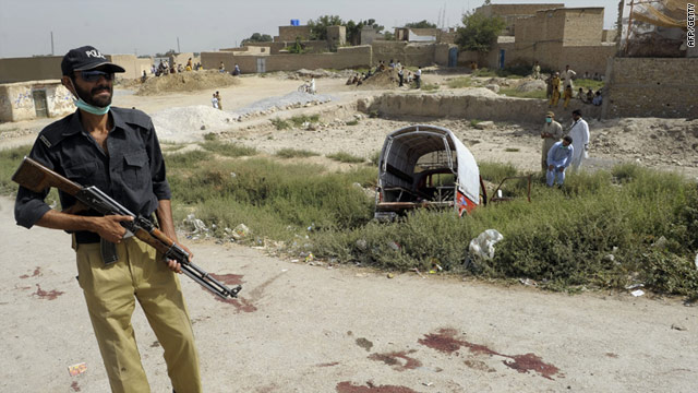 A policeman stands guard July 30 at the site of an attack on a passenger van on the outskirts of Quetta, Pakistan.