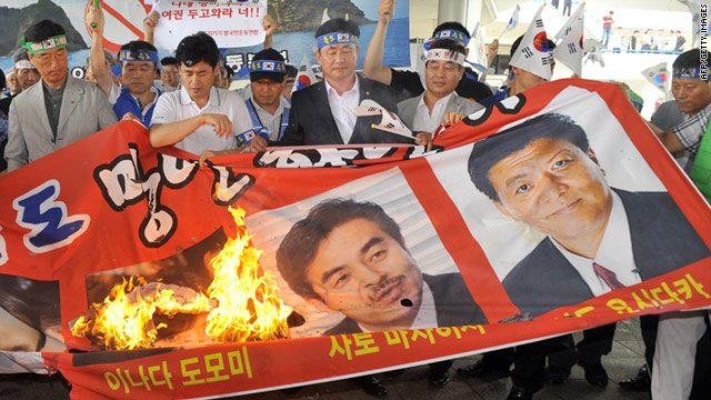South Korean protesters burn a banner showing three Japanese lawmakers ahead of their arrival in Seoul.