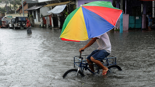 A man rides a tricycle along a flooded road in Quezon City in suburban Manila on August 2.