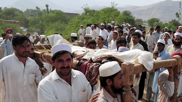 Local residents carry the body of a blast victim after Friday's suicide bomb attack.