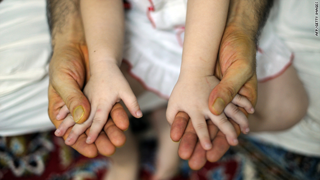 An Afghan migrant seeking a better future in Australia holds his daughter in an interview in Kuala Lumpur on August 18, 2011.