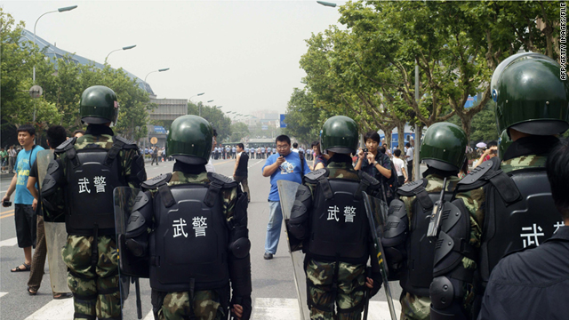 Chinese paramilitary police stand guard, as hundreds of people protest against the Fujia chemical plant in Dalian on August 14.