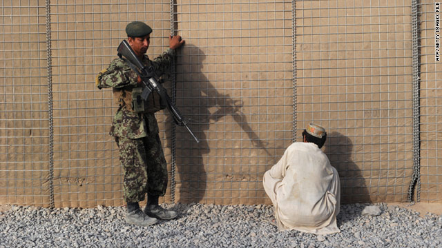 An Afghan National Army soldier guards a suspected Taliban insurgent captured by U.S. forces in the southern Afghan province of Kandahar on August 8.