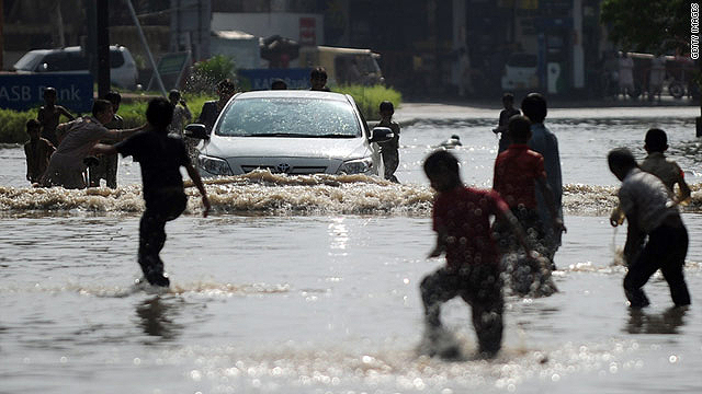 Pakistani youths play in a flooded street after heavy rains in Karachi on September 11, 2011.